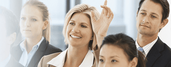 Stock image showing apeople among which a girl raised hand to ask question