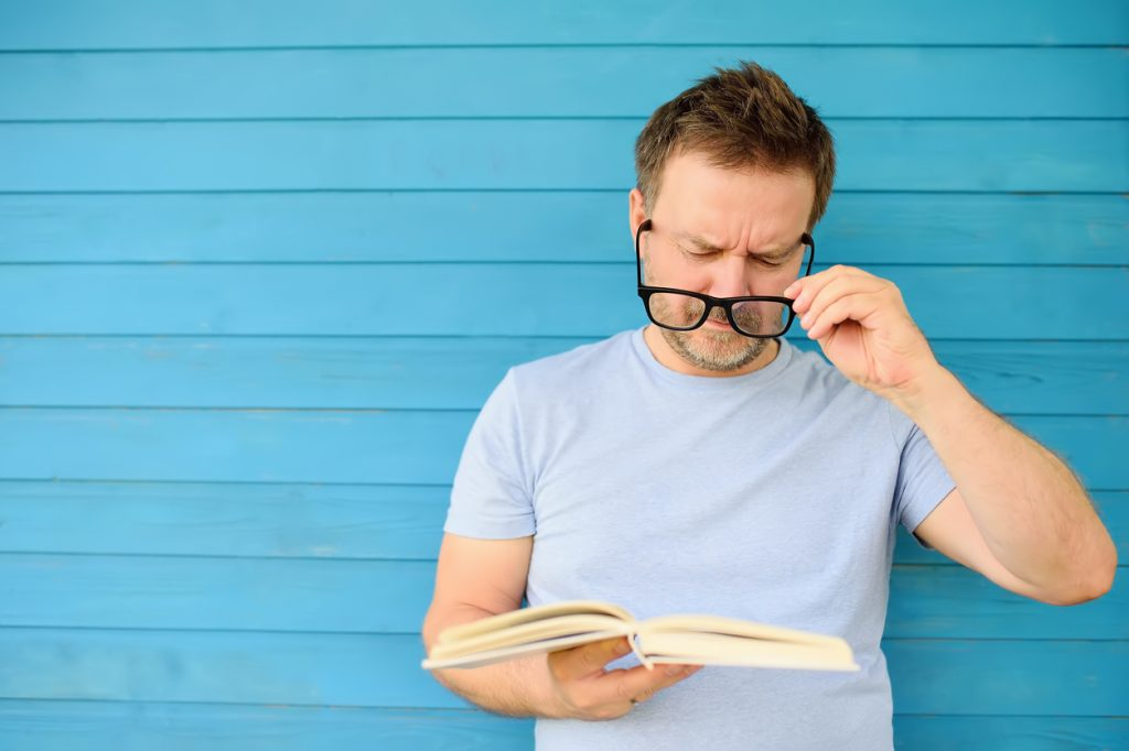 Man struggling to read with glasses in need of lasik in Los Angeles
